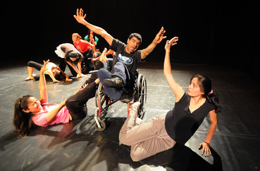 Dancer with cerebral palsy in wheelchair reaching to other dancers
